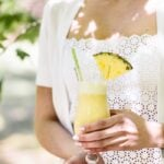 A woman is holding a glass of Pina Colada Smoothie: Frozen pineapple chunks blended with coconut milk, dates and nutmeg for a healthy morning smoothie.