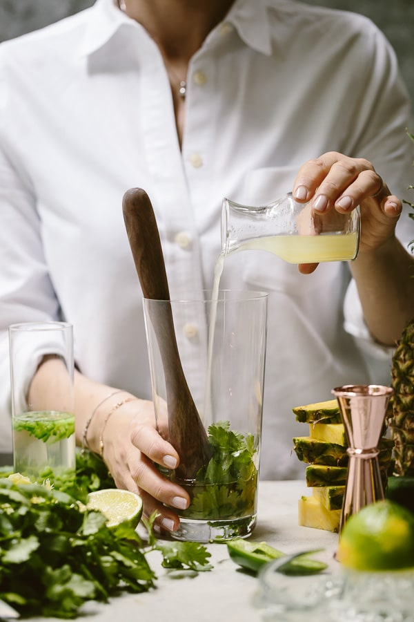 A woman is photographed as she is making a mezcal pineapple cocktail