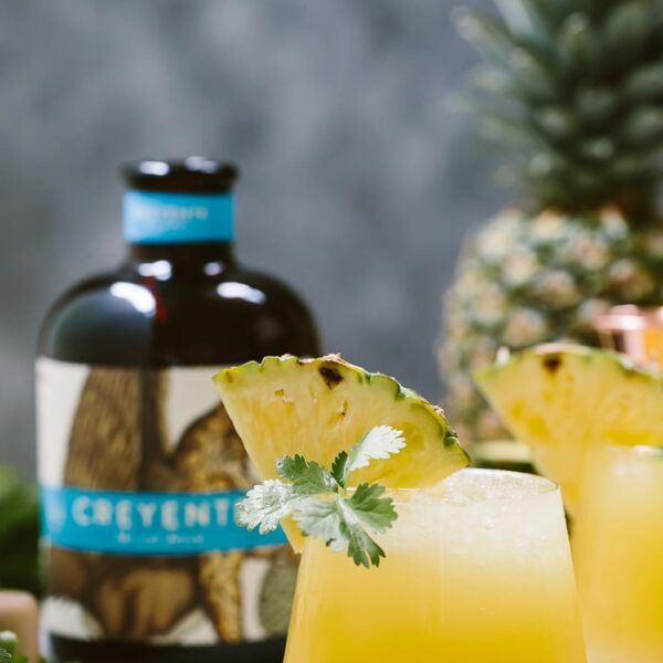 Pineapple Mezcal Cocktail garnished with a wedge of pineapple and cilantro