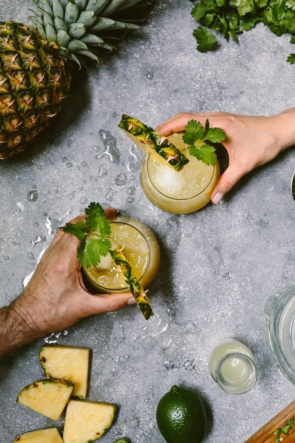 two people are about to grab mezcal pineapple jalapeno cocktail