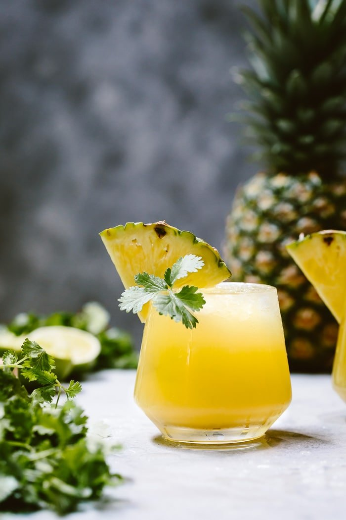 A glass of Spicy Pineapple Jalapeno Mezcalita garnished with pineapple and cilantro