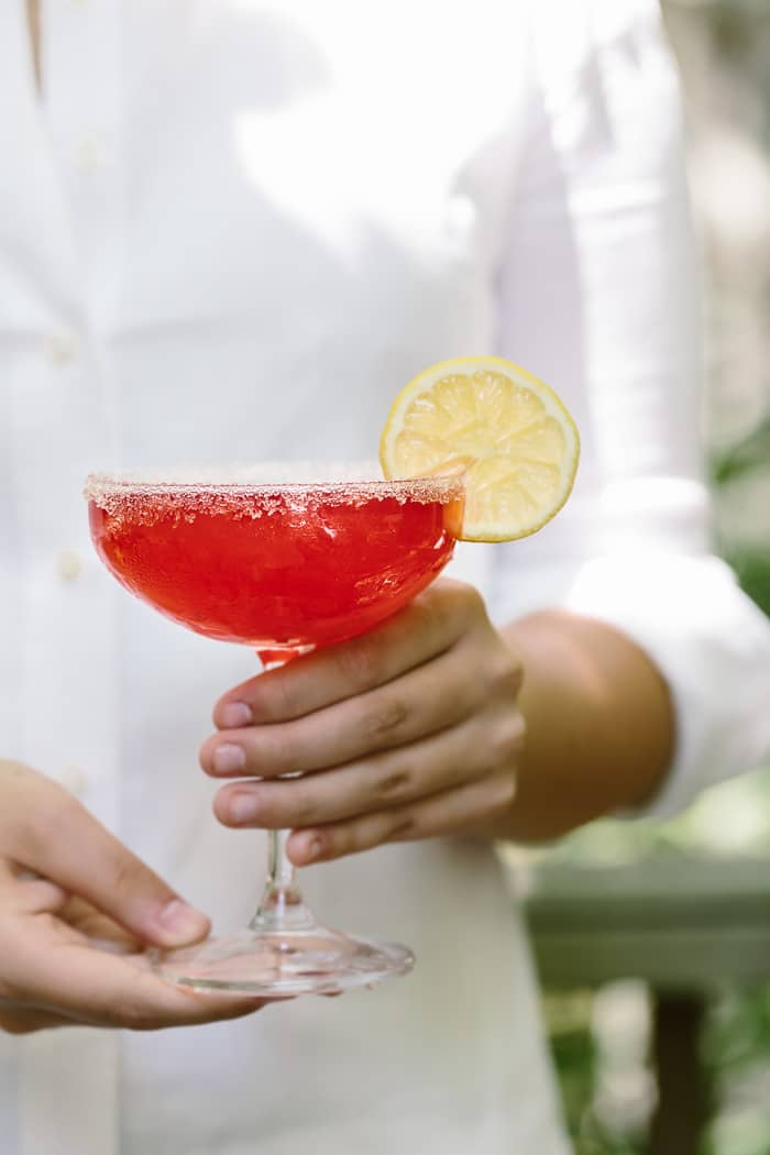 Raspberry Lemon Drop Martini with lemon garnish is photographed in the hands of a woman.