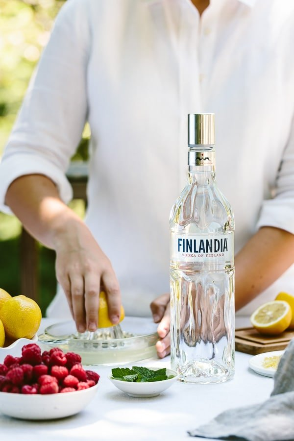A woman is squeezing lemon with fresh ingredients and vodka in the composition