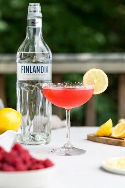 A glass of raspberry lemon drop martini garnished with lemon