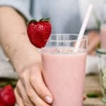 A glass full of Strawberry Banana Yogurt Smoothie is photographed from the front view as a lady is serving it.
