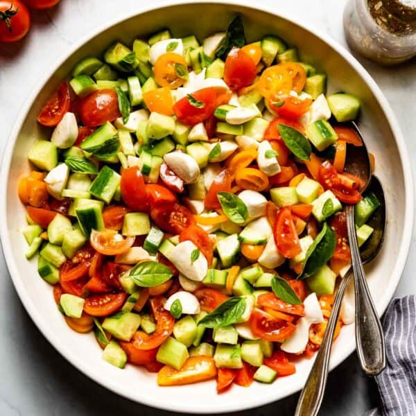 Tomato Cucumber Mozzarella salad in a bowl with spoons on the side