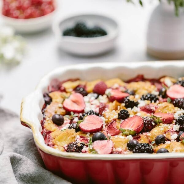 Goat cheese bread pudding with berries in a casserole dish with flowers in the background.