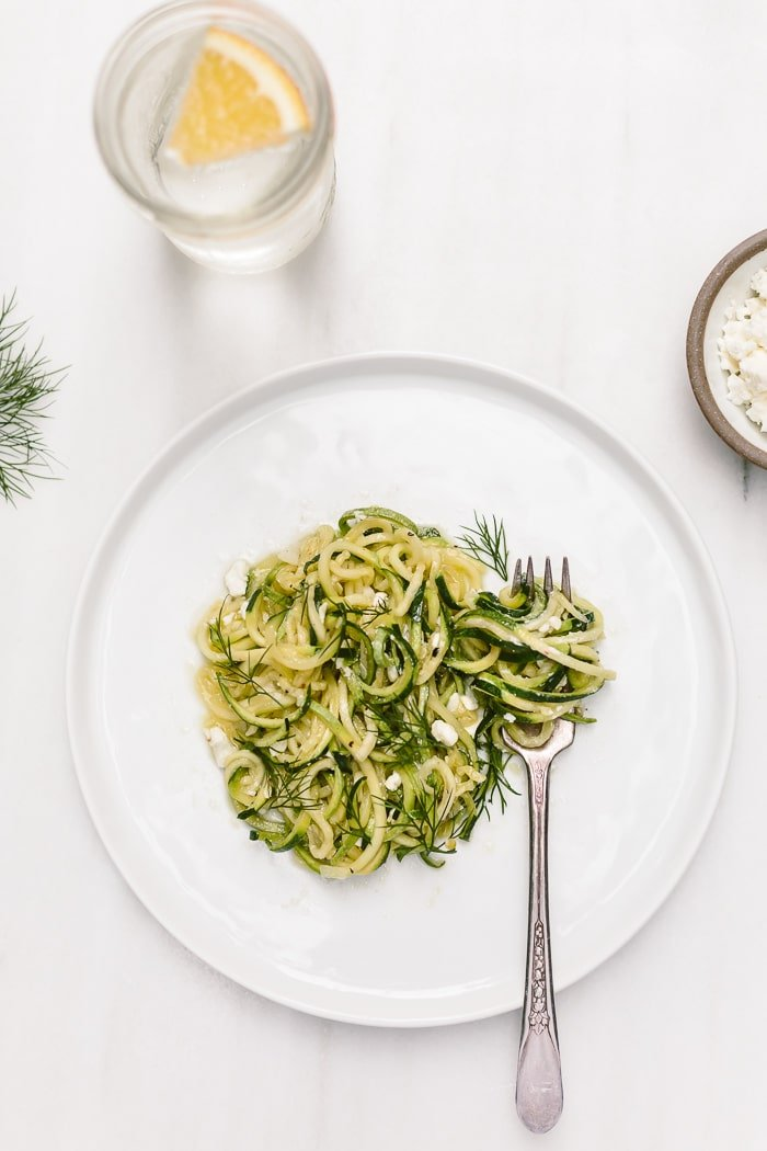 Vegetarian zucchini zoodles on a plate topped off with feta cheese and dill.