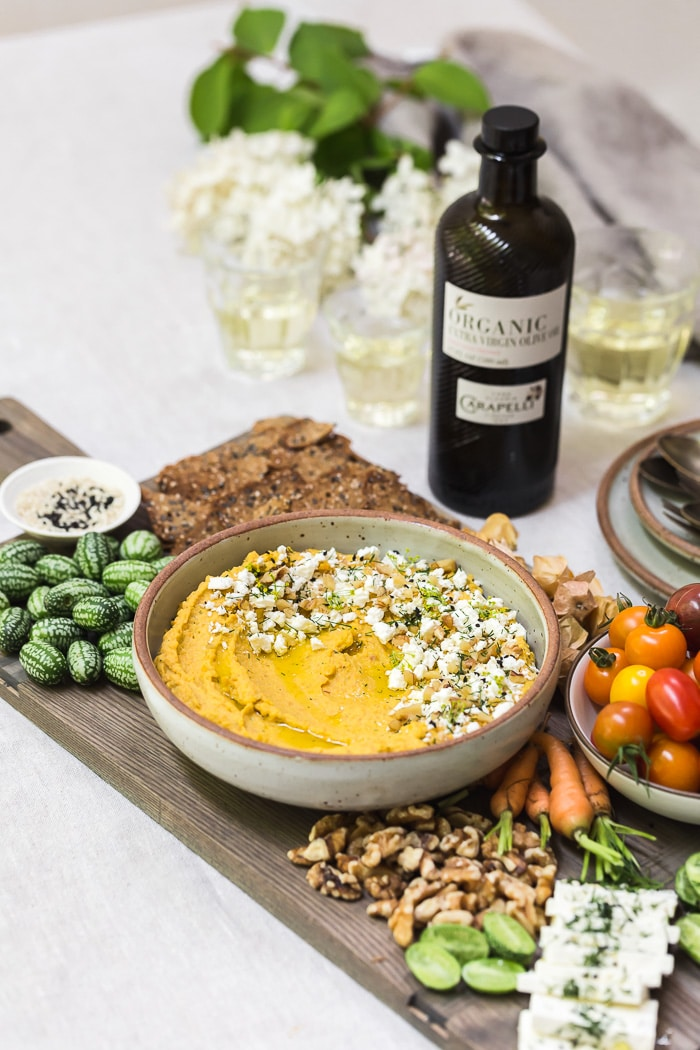 Recipe for Roasted Carrot Hummus with Feta, Dill and Walnuts in a bowl served with vegetables on the side