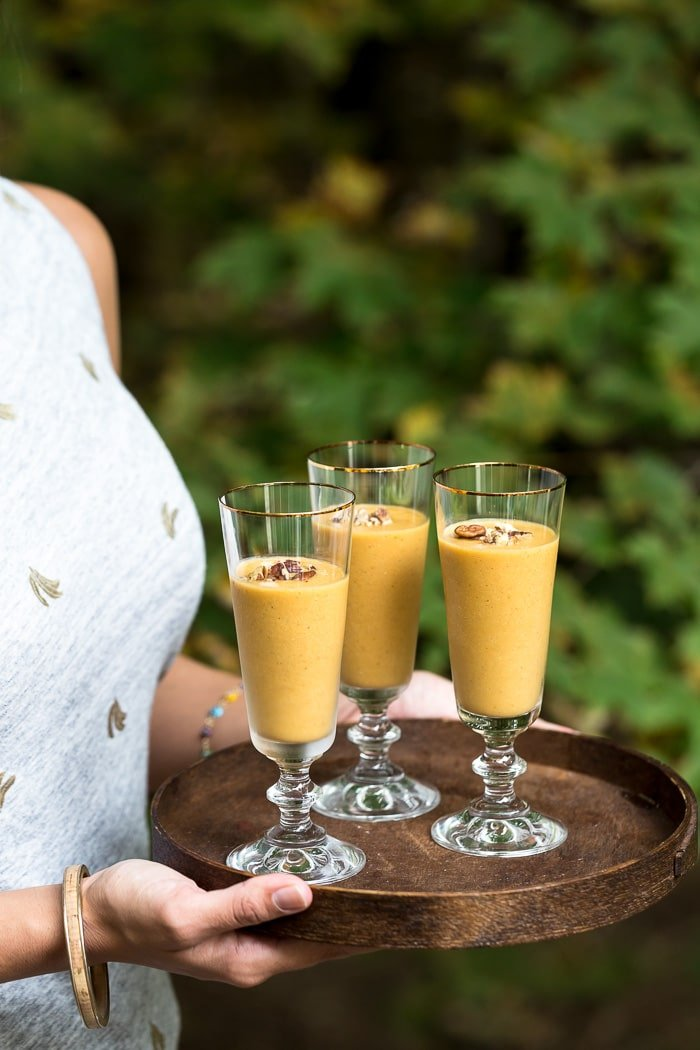 VEGAN Pumpkin Pie Protein Smoothie  on a tray being served by a woman