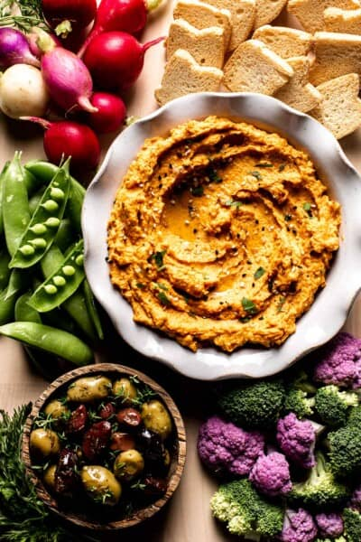 Roasted Carrot Hummus in a bowl with vegetables and olives around it