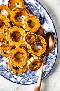 Roasted Delicata squash rings placed in an oval plated with a spoon on the side.