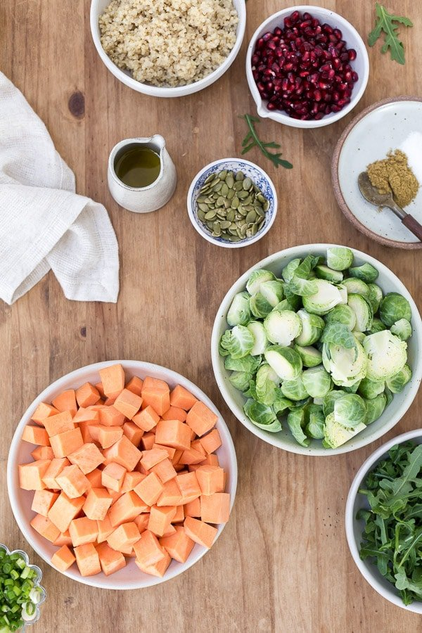 Ingredients for Roasted Brussels Sprouts and Sweet Potatoes with quinoa are laid out.