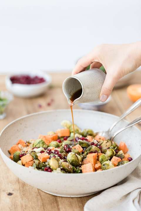 Roasted Brussels Sprouts and Sweet Potatoes are being drizzled with balsamic vinaigrette.