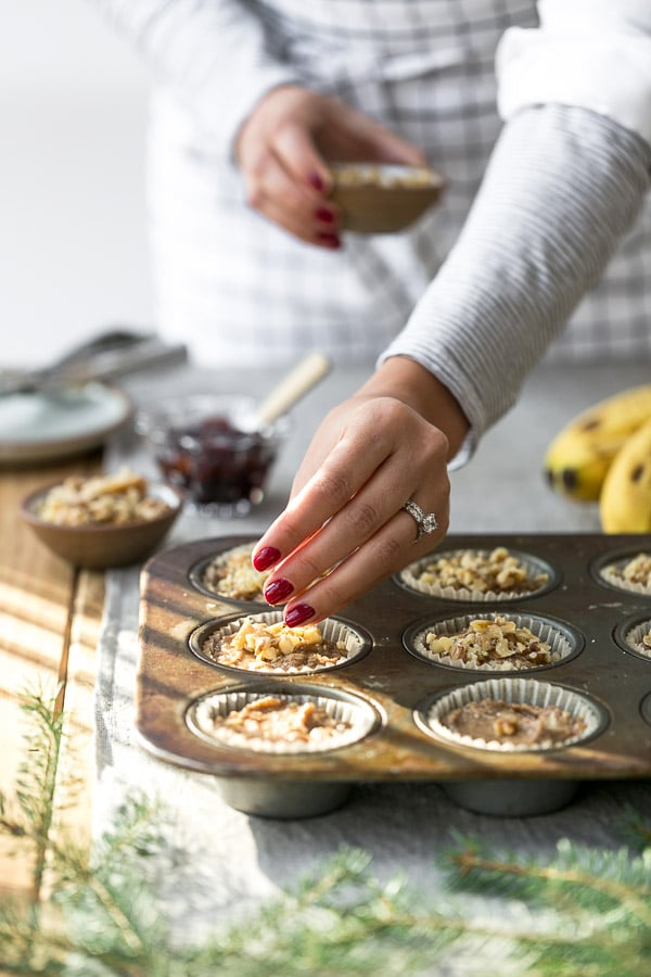 A woman is topping off banana nut muffins batter with walnuts