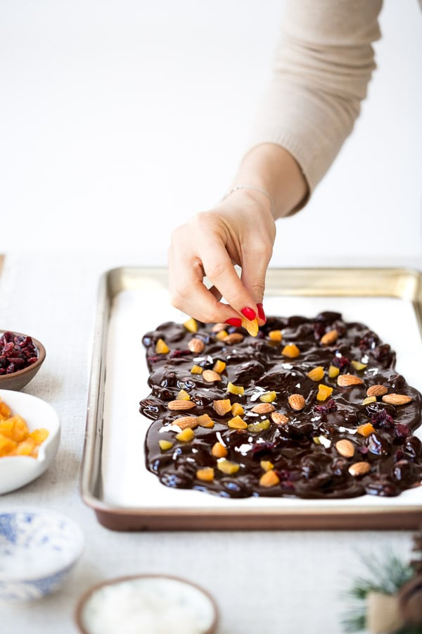Learn How to Make Almond Bark: A woman is Sprinkling the Coconut oil based and maple-sweetened Almond Bark Chocolate with dried fruits