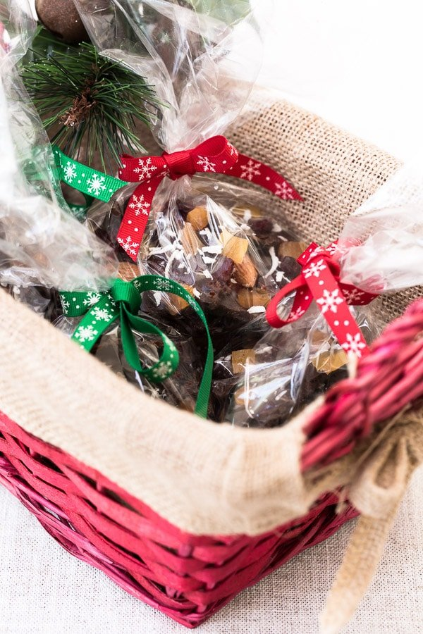 Chunks of coconut oil based and maple-sweetened dark Chocolate Almond Bark are wrapped in clear bags and placed in a basket.