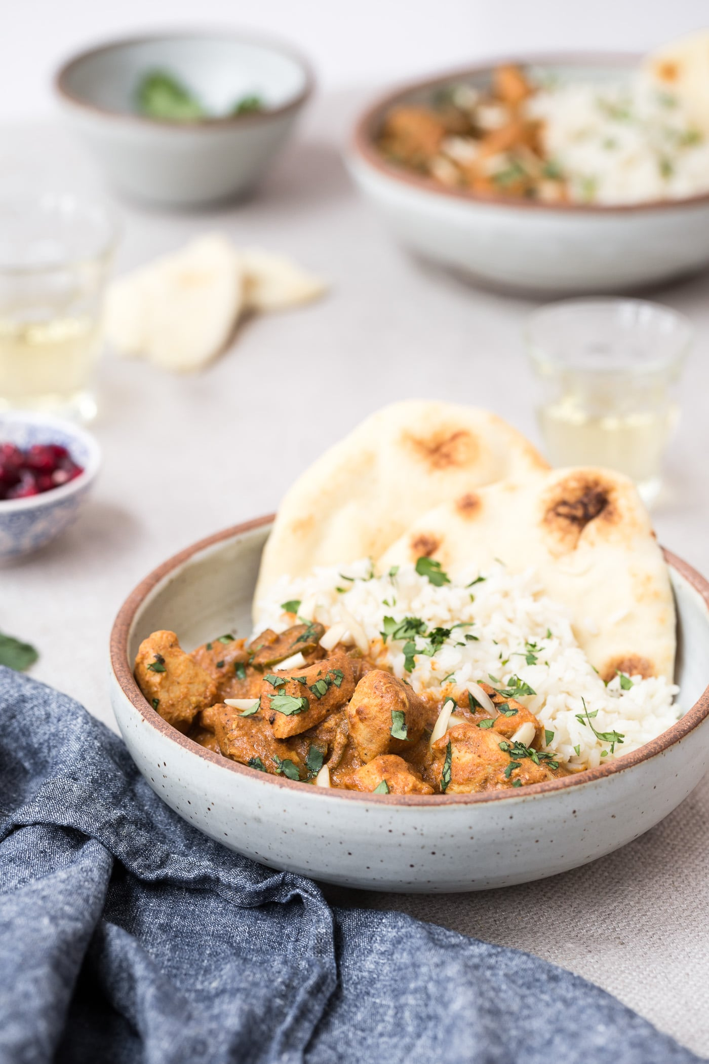 A bowl of slow cooker butter chicken served with rice and naan bread.
