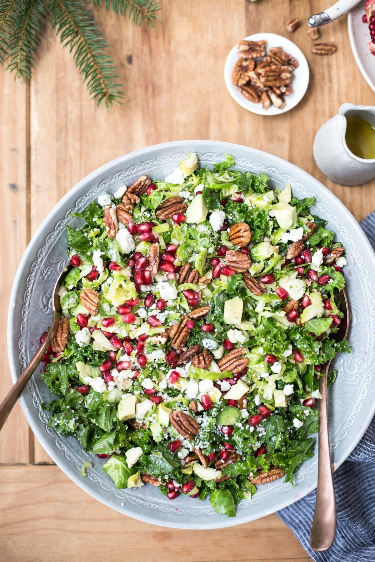 Brussels Sprout Kale Salad topped off with blue cheese, pecans and pomegranate seeds