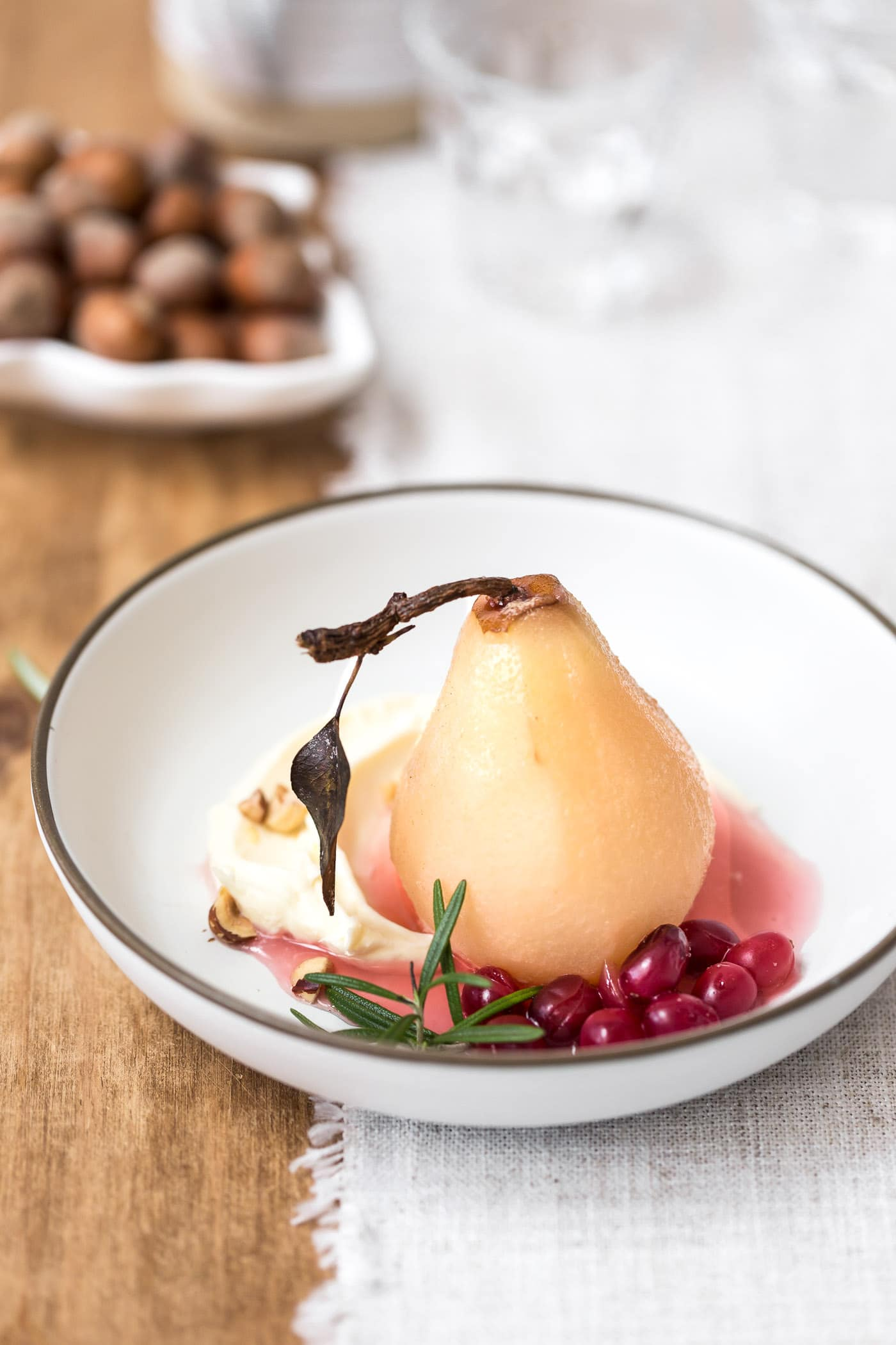 A bowl of cranberry poached pears served with mascarpone and hazelnuts