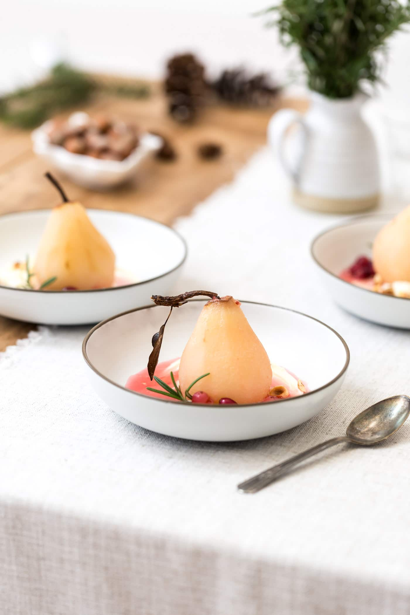 Cranberry Poached Pears are served at a table setting.