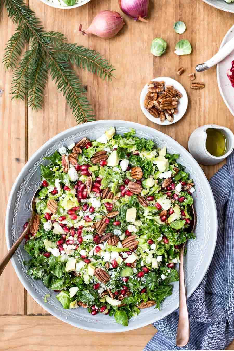 A bowl of vegetarian, colorful and festive brussels sprout kale salad recipe that is perfect for all your holiday menus.