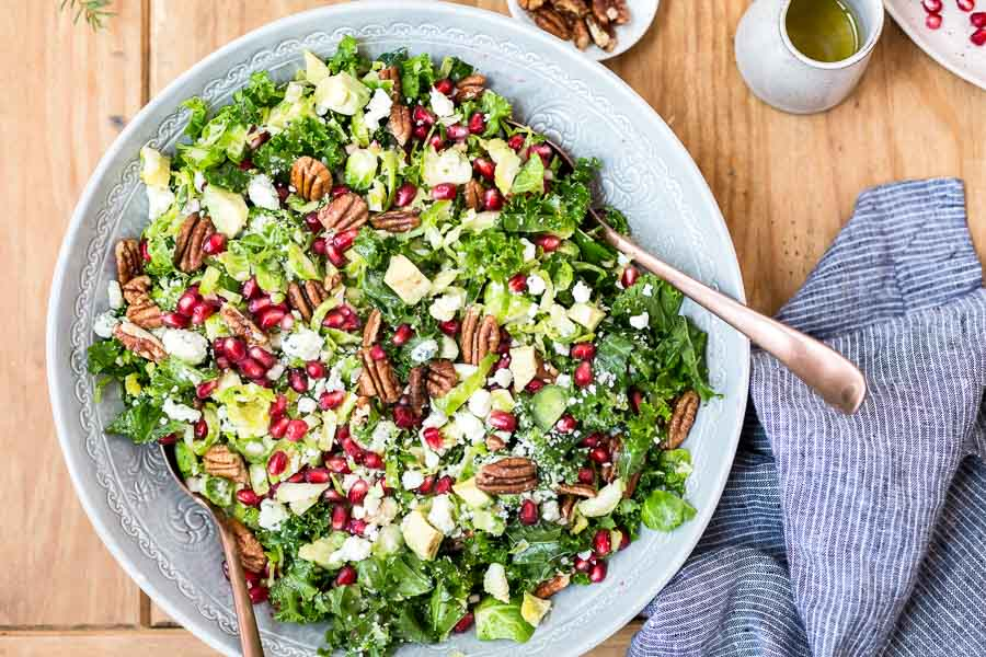 Recipe for Brussels Sprout Kale Salad - A vegetarian and colorful salad made with kale, brussels sprouts, pomegranate arils, and pecan. Perfect for the holidays.