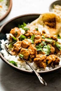 Slow Cooker Butter Chicken placed in a bowl over basmati rice