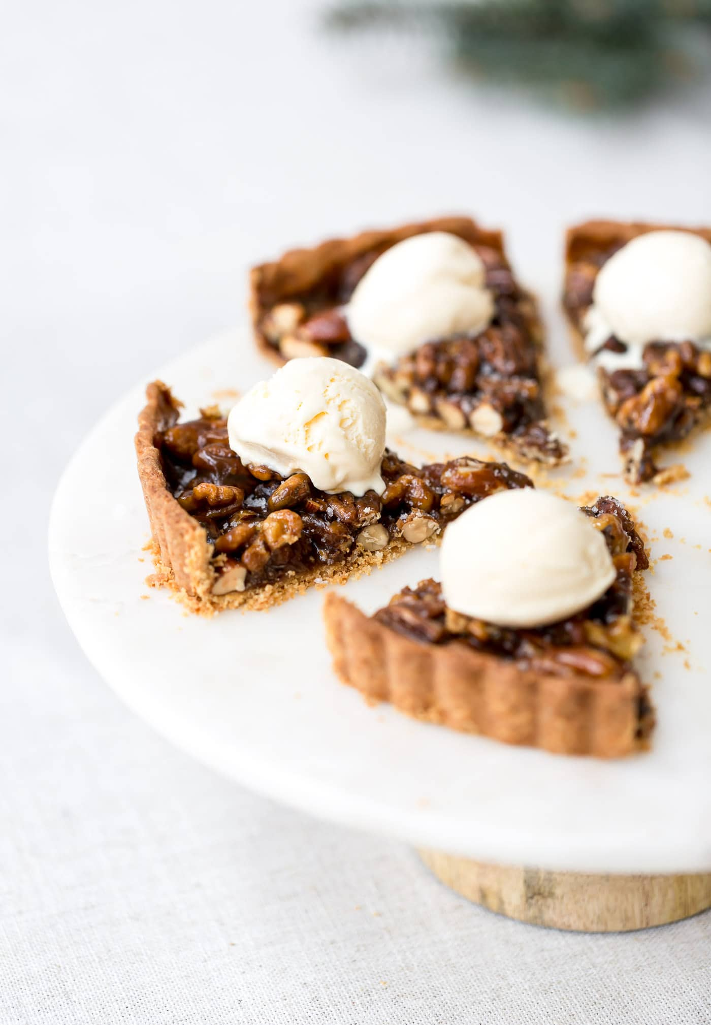 A few slices of caramel nut tart are topped off with a scoop of vanilla ice cream.