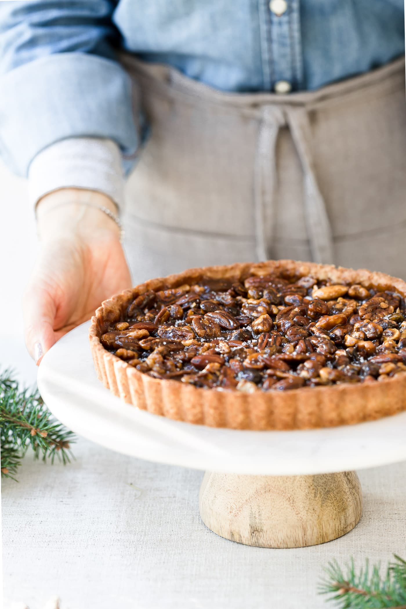 A woman is about to serve a naturally sweetened caramel nut tart.