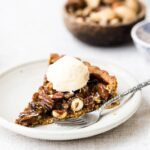 A slice of caramel nut tart topped off with a scoop of vanilla ice cream is served on a plate.