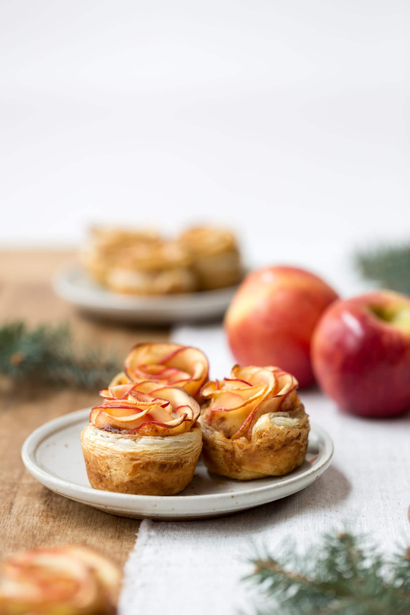 How to make apple roses - Showcasing the leaves of freshly baked apple roses served on small plates.