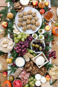A big table set up cheese, fruit, baked goat cheese balls, and other edible goodies photographed from the top view.