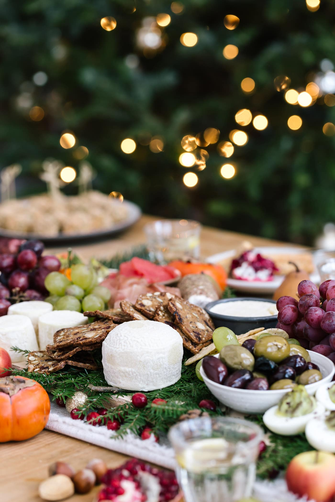 A table filled with cheese, baked goat cheese balls, fruit, olives and other edible items photographed with the Christmas tree in the background.