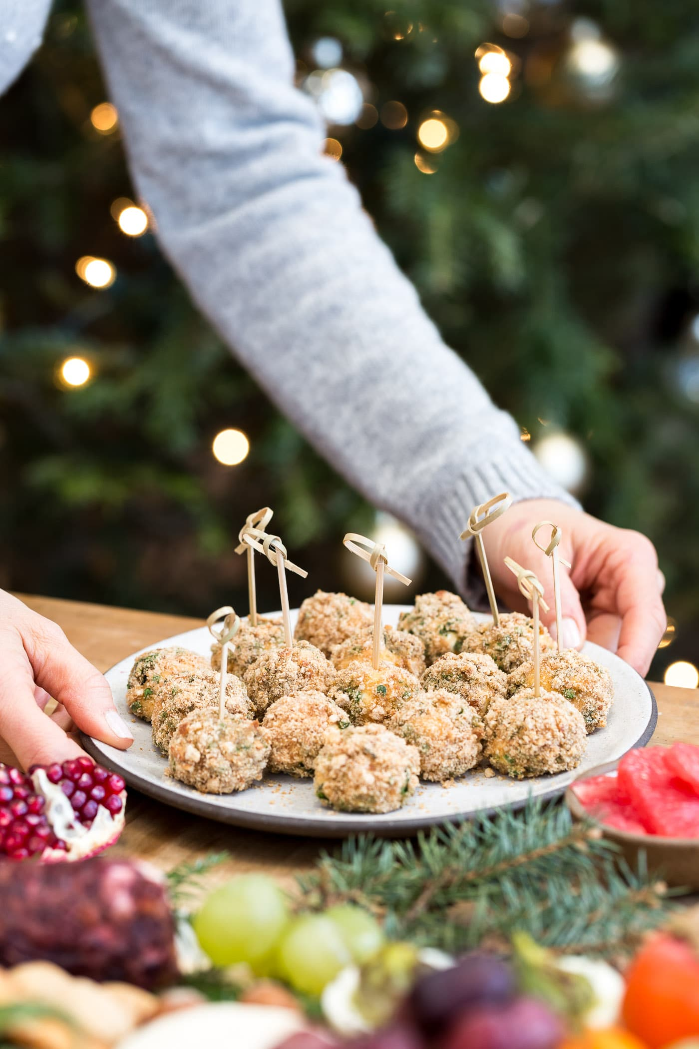 A woman is photographed as she is placing a plate of baked goat cheese balls on a plate.