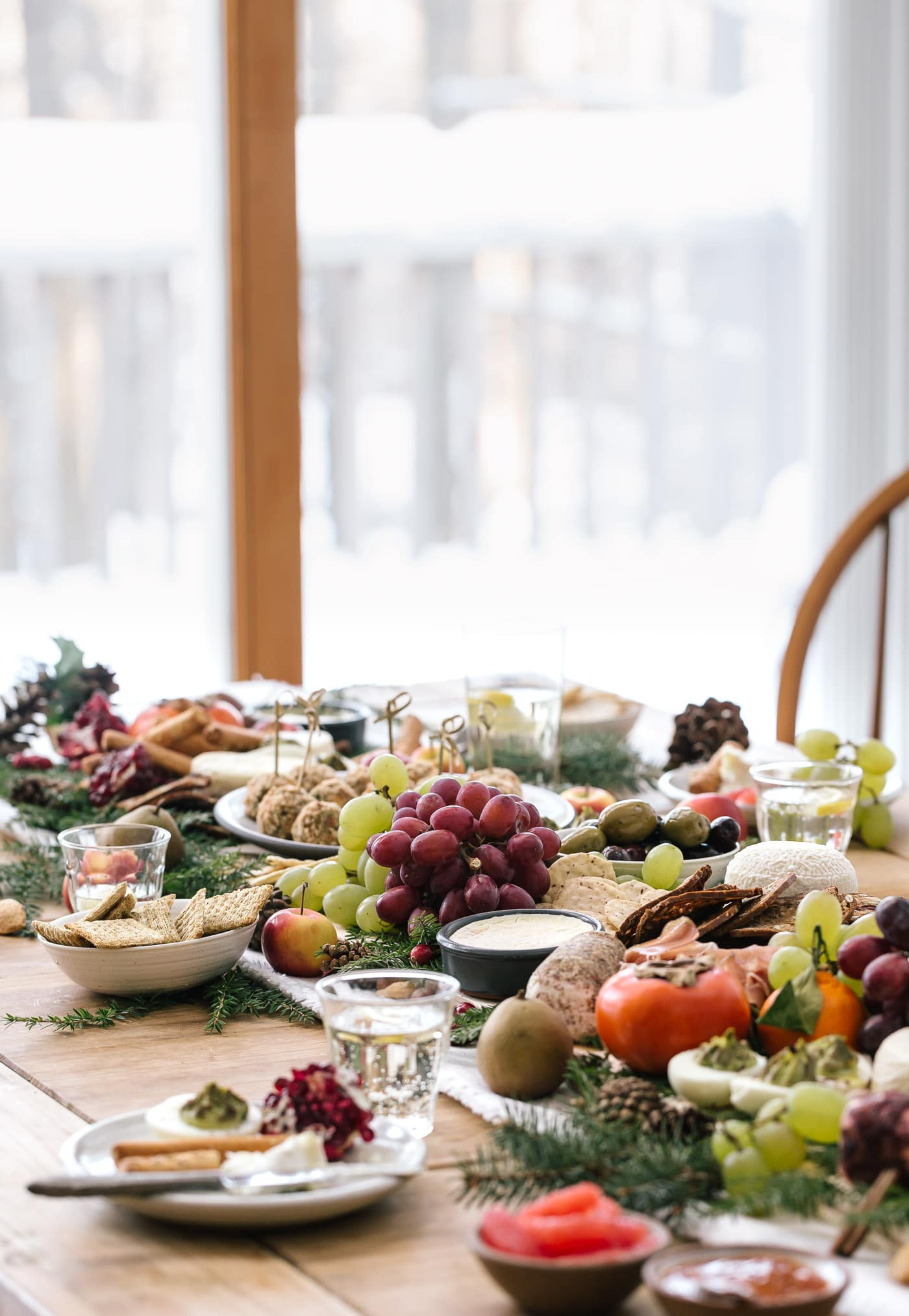 A table full of cheese, fruit and baked goat cheese balls are photographed from the front view with a snowy backdrop.