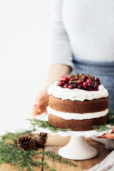 A woman is placing a gluten free gingerbread cake topped off with cranberries on the table.