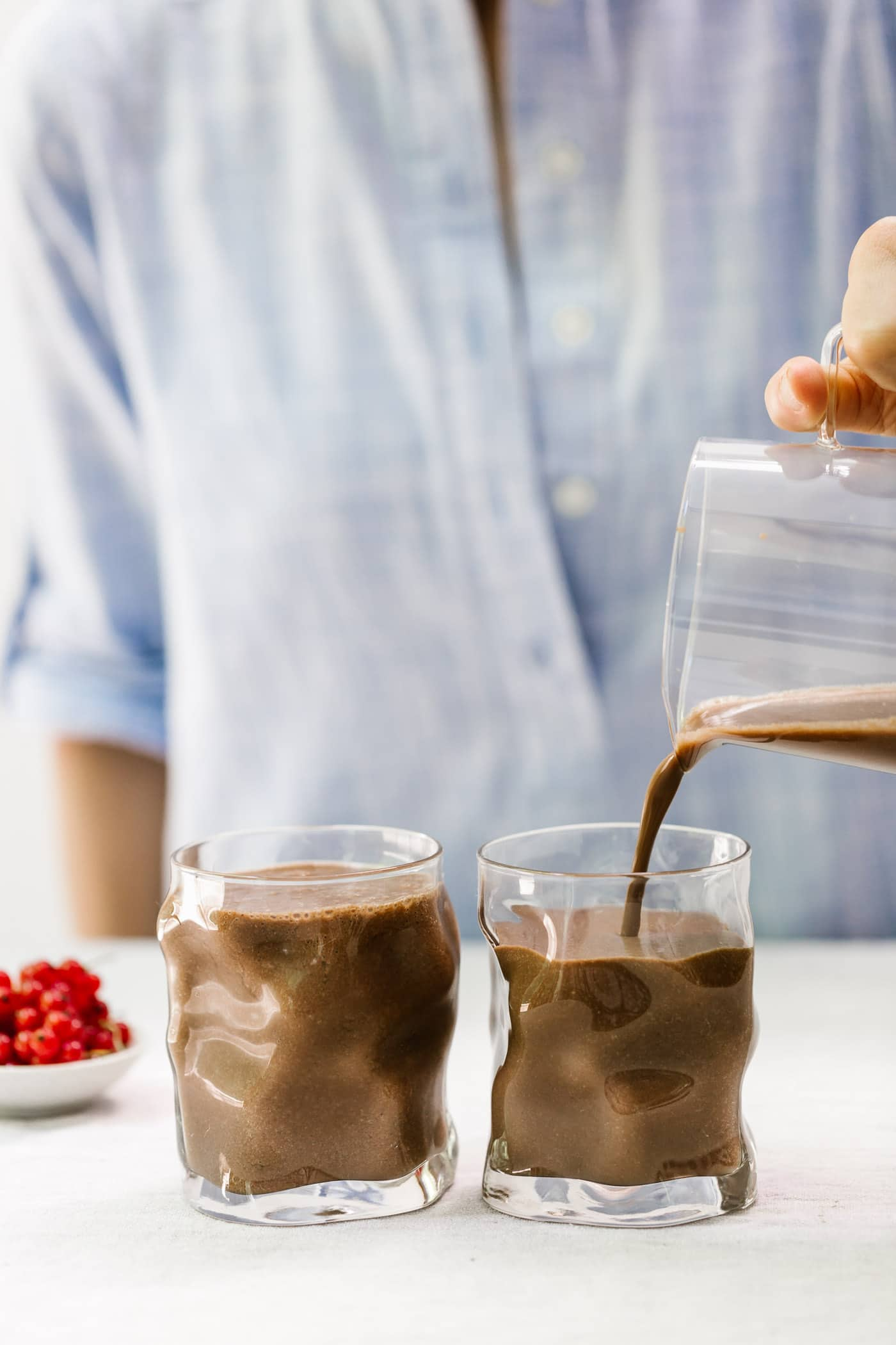 Foolproof Living's Best Chocolate Recipes For The Holiday Season: A woman is photographed from the front view as she pours Nutella Lover's Healthy Chocolate Smoothie