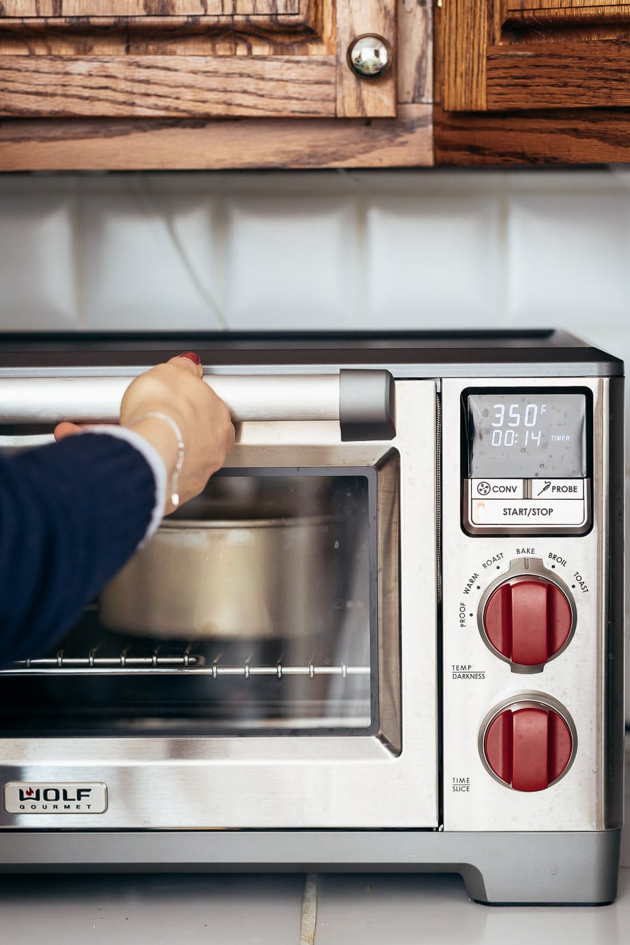 A woman is about to open an oven door with two gluten free gingnread cake inside.