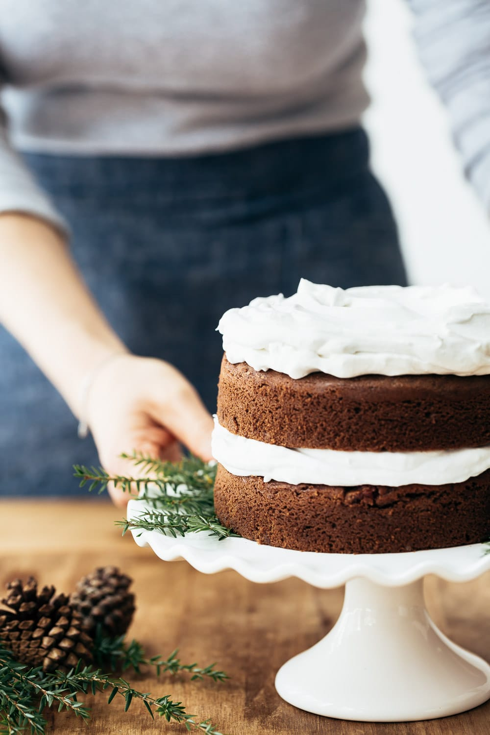 A woman is photographed from the front view as she is getting ready to garnish a Coconut Flour Gingerbread Cake with cranberry topping.