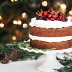 A Gluten Free Gingerbread Cake is photographed from the front view in front of a Christmas Tree.