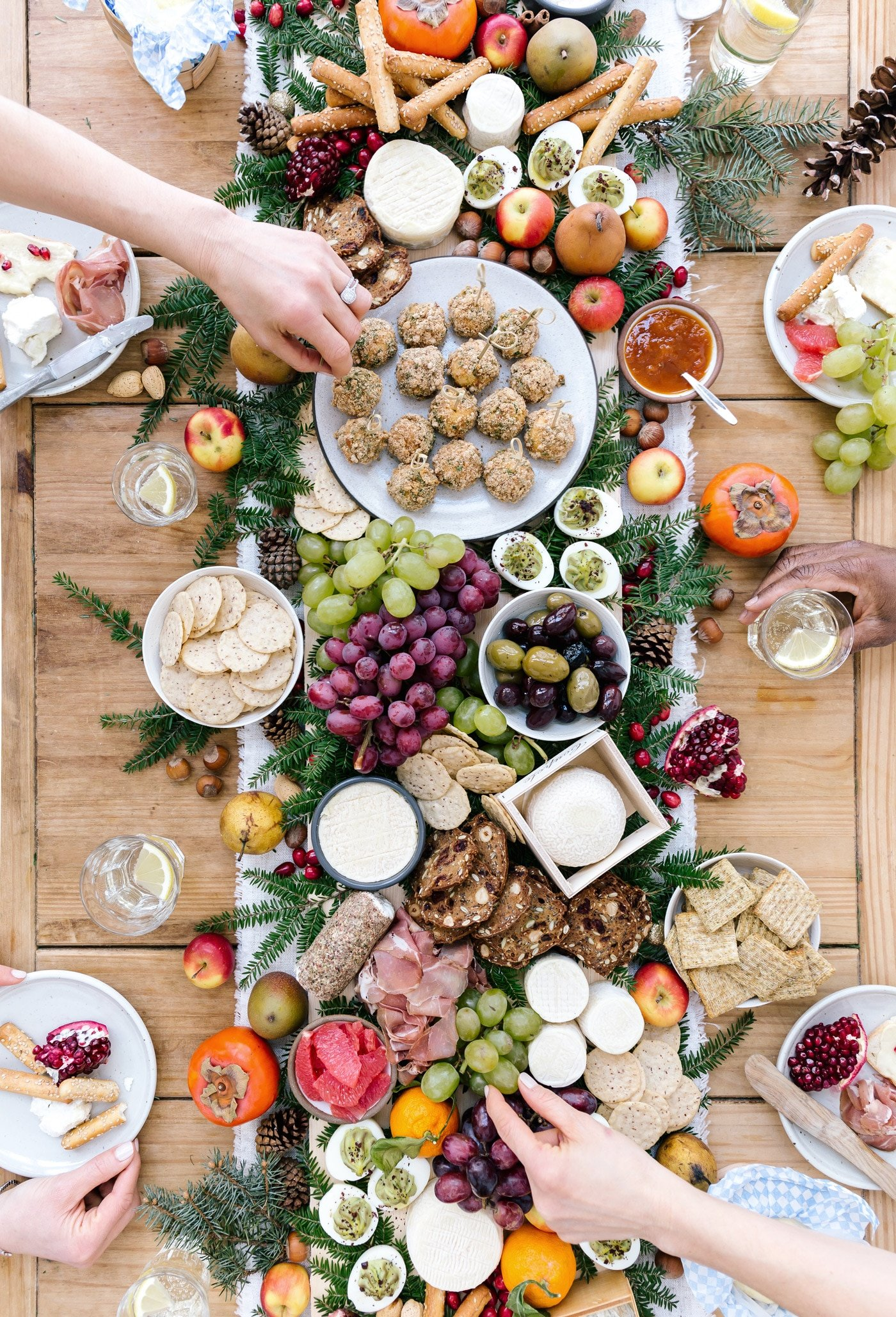 A big table set up cheese, fruit, baked goat cheese balls and people are serving themselves.