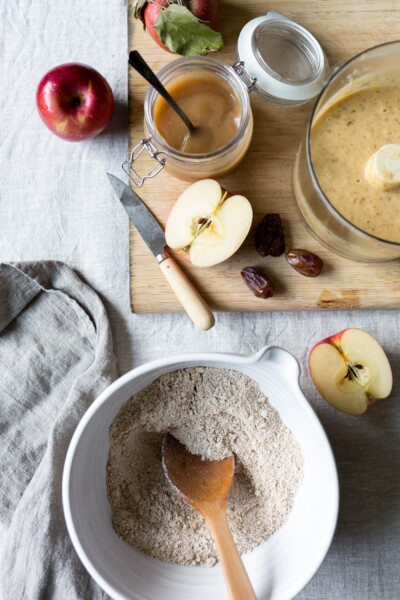 8 Last minute recipes for Christmas Baking. A big bowl of flour and sliced apples are prepped to make the batter for apple almond muffins