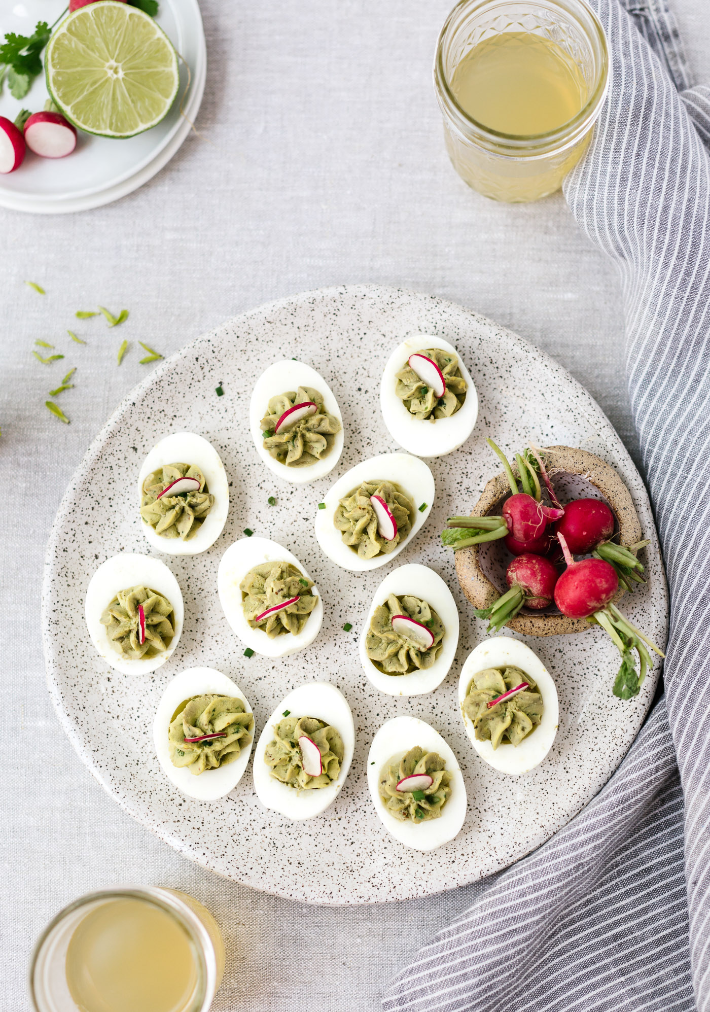 Avocado Deviled Eggs garnished with radishes photographed from the top view.
