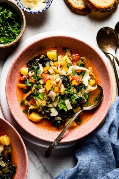 Tuscan Kale Soup in a bowl with a spoon on the side
