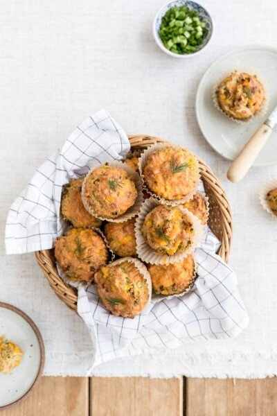 A basket full of freshly baked savory corn muffins along with a few half eaten ones are photographed from the top view.
