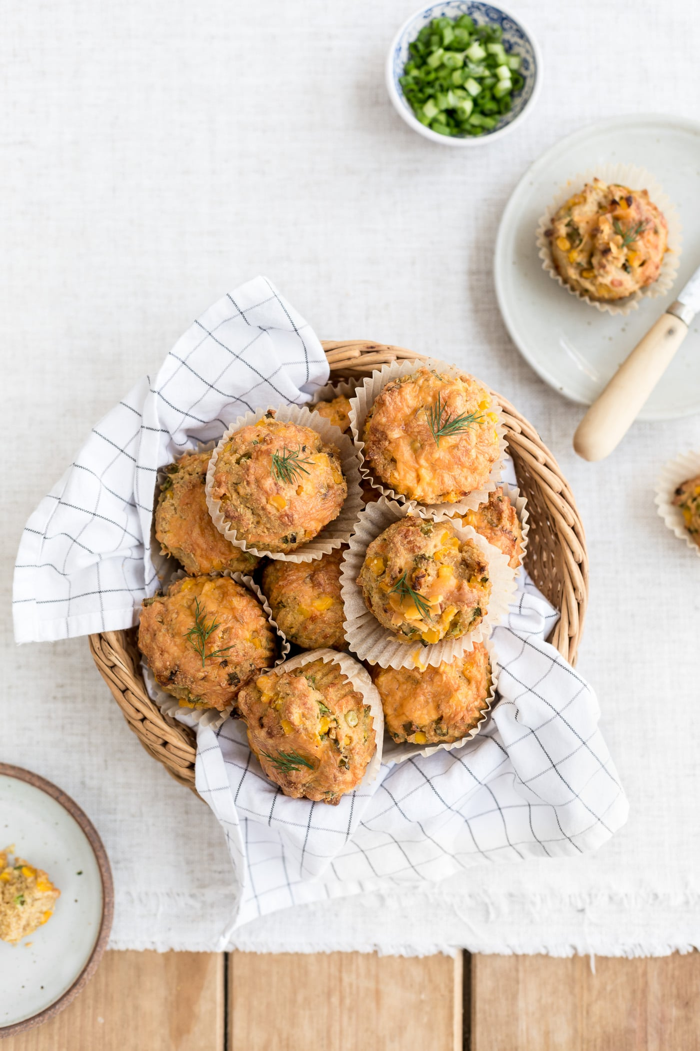 A basket full of freshly baked cornbread muffins along with a few half eaten ones are photographed from the top view.