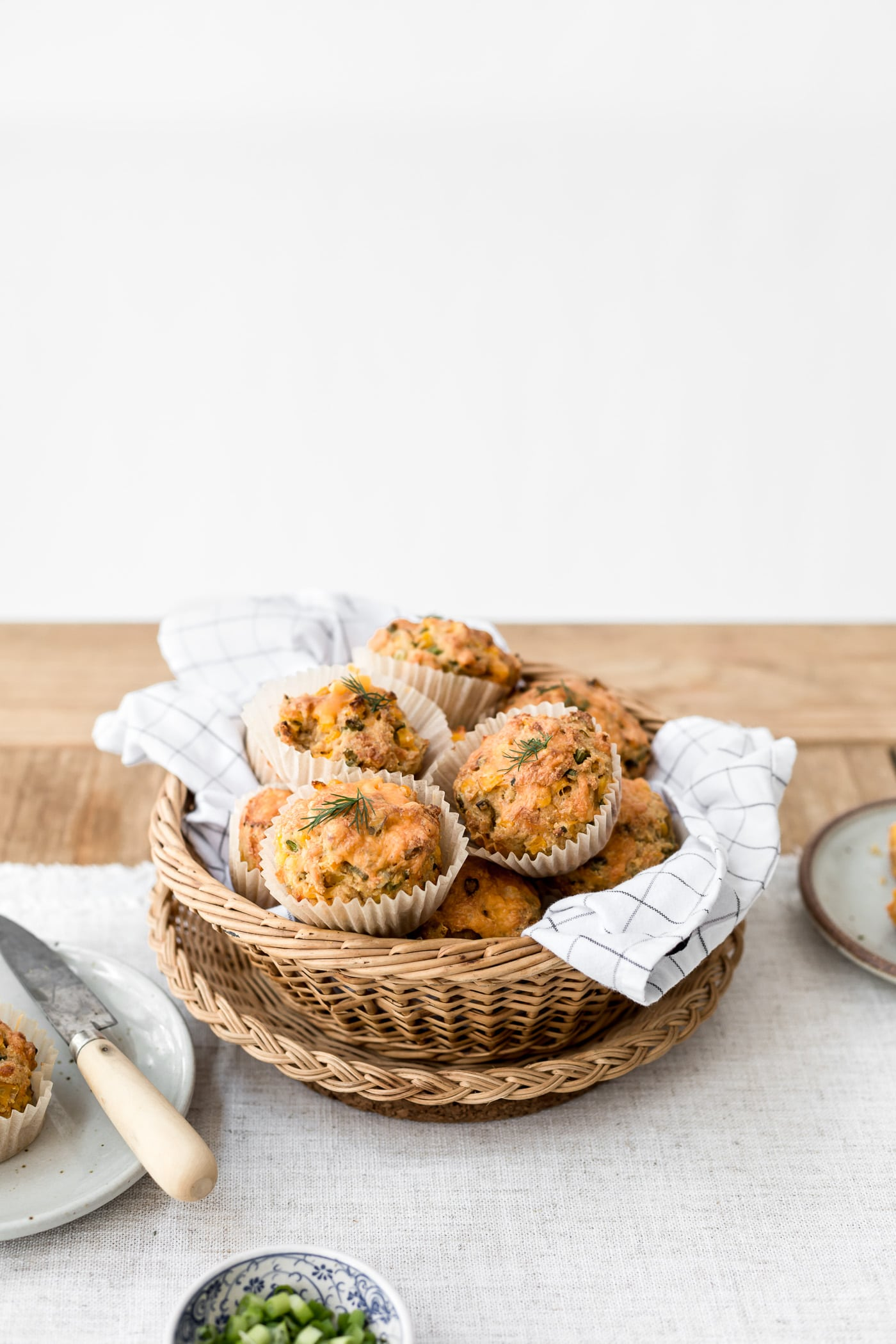 A basket full of freshly baked cornbread muffins are photographed from the front view.