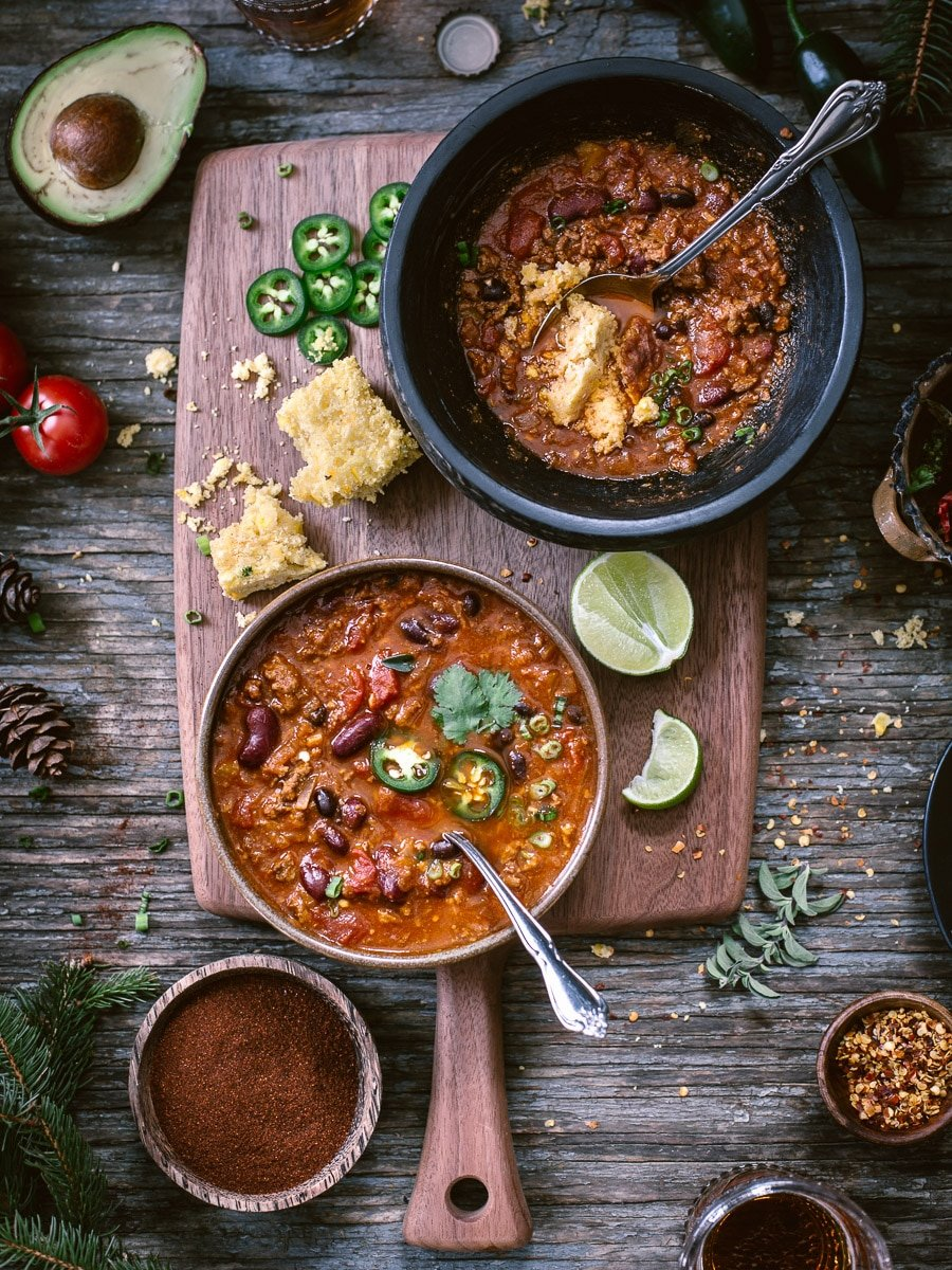 Two bowls of heartwarming turkey and bean chili photographed from the top view along with chili powder, avocado, cornbread and sliced jalapeno pepper on the side.