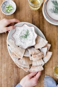 A woman is photographed from the top view as she is serving tzatziki sauce with pita bread.